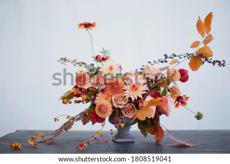 Beautiful flower composition with autumn orange and red flowers and berries. Autumn bouquet in vintage vase on a white wall background Сток-фото ©