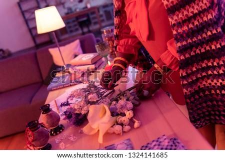 Beautiful flowers. African american plump fortune-teller wearing golden watch spreading flowers