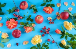Beautiful flowers and apples on a blue background