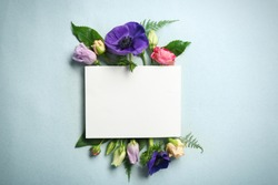 Beautiful flowers and green leaves as floral frame and paper card on light background