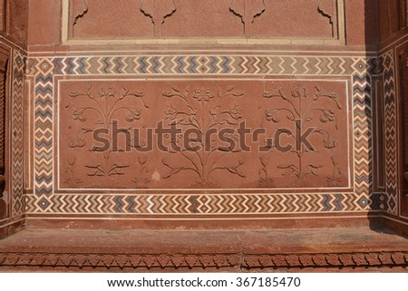 Beautiful flowers carved in red sandstone surrounding by the colorful gemstone inlay at Mosque in Taj Mahal (UNESCO World Heritage Site) #367185470