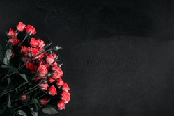 Beautiful flowers dark composition. Pink rose flowers on black stone background. Flat lay, top view, copy space