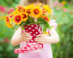 Beautiful flowers in red boots against spring background