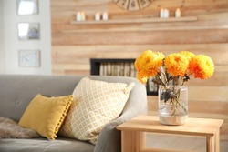 Beautiful flowers in vase on table in room, closeup. Cozy interior inspired by autumn colors
