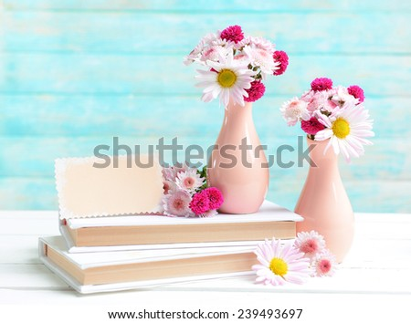 Beautiful flowers in vases on table on light blue background