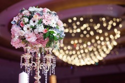 Beautiful flowers stand on table in the wedding ballroom