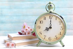 Beautiful flowers with clock and book on table on light blue background