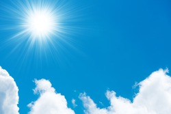 Beautiful fluffy white clouds on bright blue sky and shining sun with sun rays
