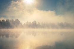 Beautiful foggy morning. Lake coast. Fog over autumn lake water.