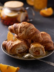 Beautiful food photo with breakfast: tea and croissants with orange jam. Food styling, black background.
