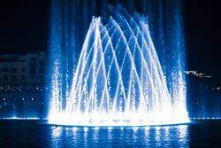 Beautiful fountain at night illuminated with blue light.