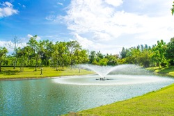 Beautiful fountain on the lake with a Blue sky and clouds in the park