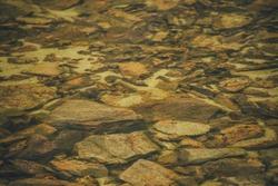 Beautiful fragment of orange stony bottom of mountain lake with transparent water. Colorful minimal nature background with many orange stones with mosses and lichens on bottom of mountain lake.