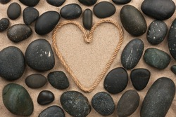 Beautiful frame of rope in the form of heart with black stones, on the sand