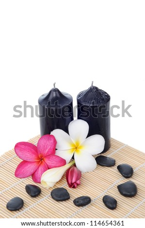 beautiful frangipani flowers with candles and spa stone isolated on white background