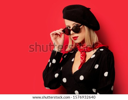 beautiful french woman in beret on red background