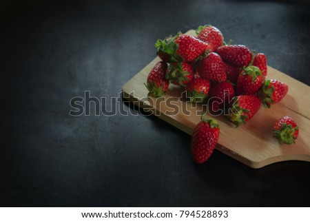 Stock Photo Beautiful fresh red strawberry on wood cream chopping or cutting board on wood black table background, yummy or delicious healthy fruit in summer concept