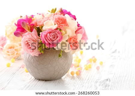 Beautiful fresh spring flowers in pot on wooden table, closeup