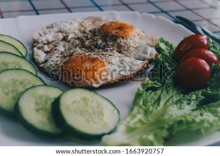 Beautiful fried eggs with tomatoes and cucumbers on a plate Сток-фото ©