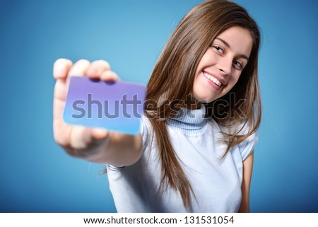 beautiful friendly smiling confident teen girl showing card in hand, over blue background