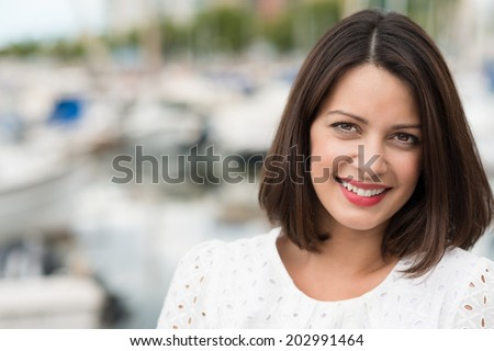Beautiful friendly young woman with shoulder length brown hair posing outdoors looking directly at the camera with a gentle smile