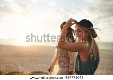 Beautiful friends enjoying a walk on the beach on a sunny day. Two young women walking together on a beach.