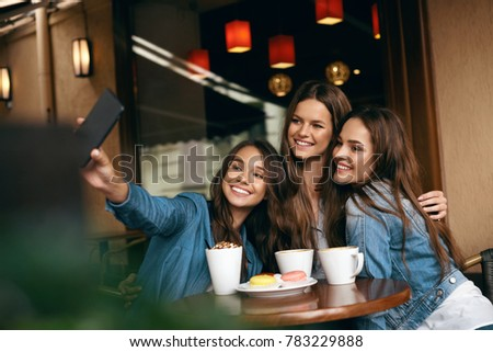 Beautiful Friends Taking Photos In Cafe. Portrait Of Beautiful Girlfriends With Cups Of Coffee And Biscuits Laughing And Having Fun Sitting In Coffee Shop. High Resolution. Foto d'archivio ©