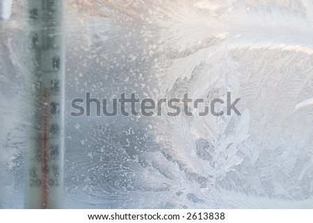 beautiful frosty window with thermometer, good background for greeting-cards, thermometer is out of focus, focal point on frosting. - stock photo