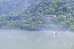 beautiful fuchun river scene, misty houses by the riverside, hangzhou city, zhejiang province, China