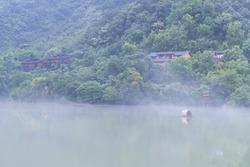 beautiful fuchun river scene, misty houses by the riverside, hangzhou city, zhejiang province, China