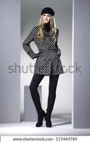 Beautiful full body young fashion model in coat posing light background - stock photo
