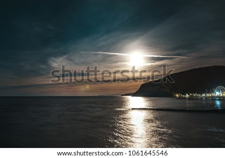 Stock Photo beautiful full moon over the mountain and the sea.
