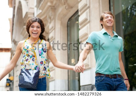 Beautiful fun ethnically diverse young couple enjoying city break holiday trip, holding hands running together in shopping street exclusive stores, laughing. Consumers leisure recreation lifestyle.