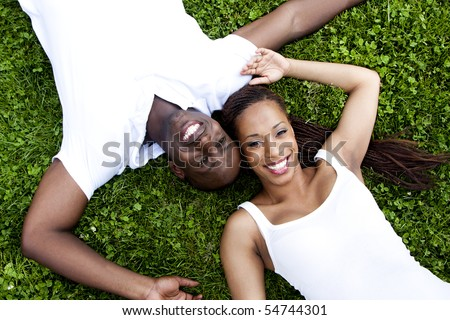 Beautiful fun happy smiling African American couple wearing white shirts laying in grass, faces of woman and man next to eachother in opposite direction. - stock photo