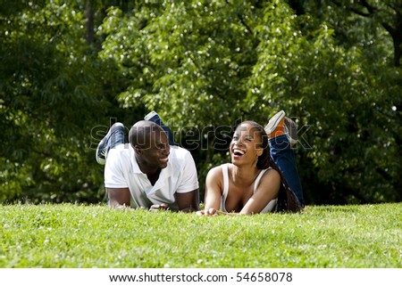 Beautiful fun happy smiling laughing African American couple joking laying on grass in park, wearing white shirts and blue jeans.