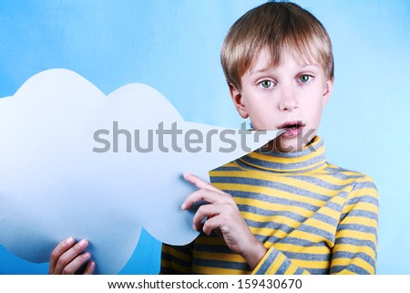 Beautiful funny blond boy holding a blank blue message cloud saying something over blue background