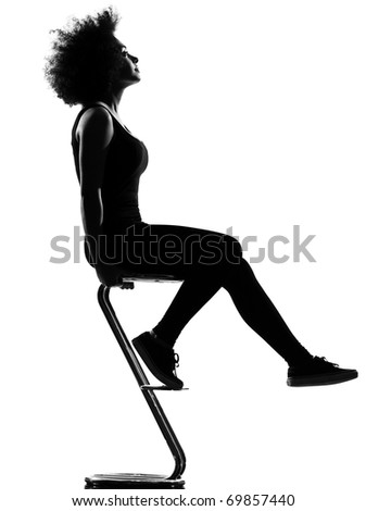 beautiful funny young afro american woman sitting on footstool pensive in silhouette shadow on studio isolated white background