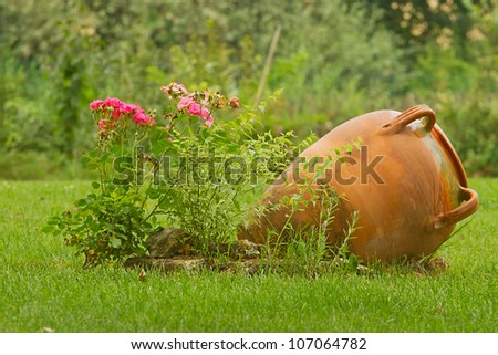 Beautiful garden decoration with amphora and roses