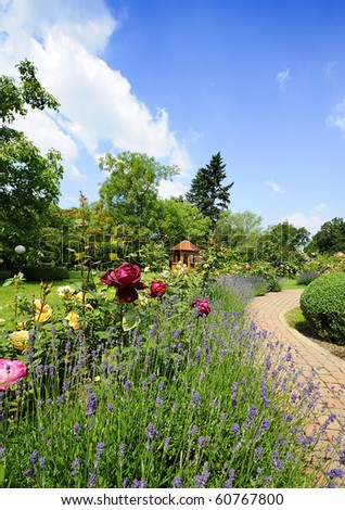 Beautiful garden with blooming roses, brick path and a small gazebo