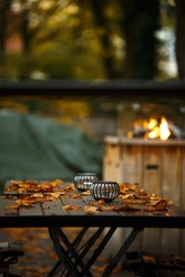 Beautiful garden with fireplace. Table with candles covered by autumn orange leaves.