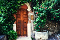 Beautiful garden with old antique door, flowers and ivy. Vintage European cute entrance in a house