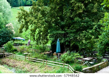 Beautiful garden with wooden fence, small river and bridge plus several chairs, tables and umbrellas