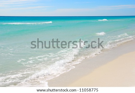 Beautiful gentle waves on pristine beach with turquoise colored water - stock photo