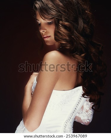 Beautiful gentle woman with curly hair in white fashion dress on a brown background
