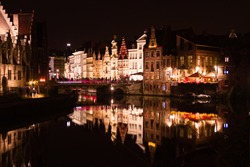 Beautiful Ghent (Belgium) during night time when the lights shine on the historic buildings while people eating their diner