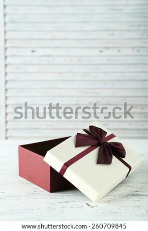 Beautiful gift box on white wooden background #260709845