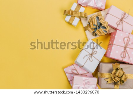 beautiful gift boxes wrapped in paper with red, gold and pink ribbon on a yellow surface. Top view  #1430296070