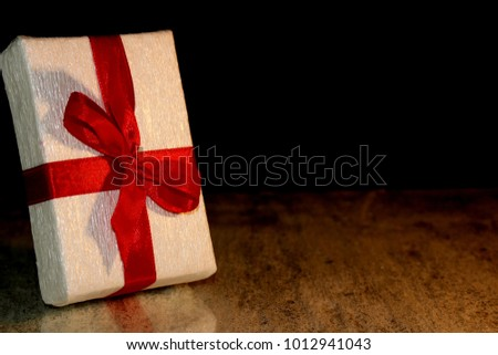 beautiful gift tied with a red ribbon on a black background #1012941043