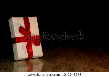 beautiful gift tied with a red ribbon on a black background #1012943968