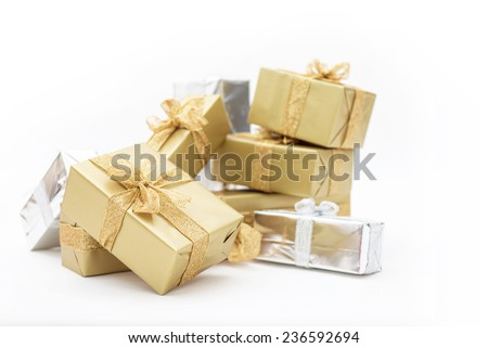 Beautiful gifts in gold and silver packaging for Christmas, holidays, isolated on white background. Sparkling ribbon with glitter on presents